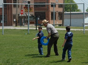 Superintendent Dennis Vasquez plays a game with two boy scouts on the historic playground with the historic backstop in the background during a previous Scouting Day.