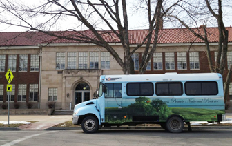 Bus with image of tallgrass prairie painted on it, parked in front of Brown v. Board of Education National Historic Site entrance.