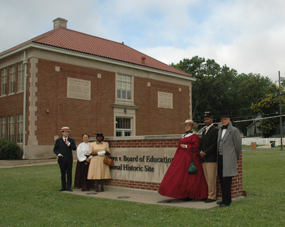 Six reenactors, from the 1850s to the 1950s, stand next to the site's sign.