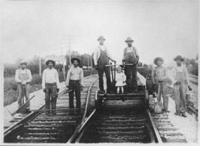 An image of seven adult immigrant mexican men and one little girl. The men were part of the Atchison, Topeka, and Santa Fe section crew, Pauline, Kansas.