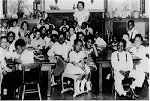 Black children sitting in desks in classroom with teacher