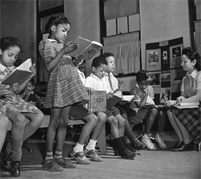 African American girl standing and reading with other children and teacher in the background.