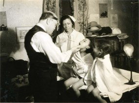 Two African American children being examined by a doctor with a nurse standing nearby.