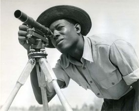 African American man looking through a surveyor's scope.