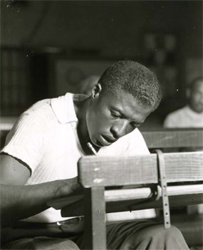 An African American man writing at a desk.