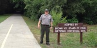 Ranger Randy stands next to the Landon Trail at a sign recognizing our adoption of a section of the trail for cleanup.