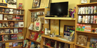 Books and videos on shelves in bookstore.