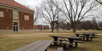 View of the four handicapped-accessible picnic tables looking towards the historic playground and the site.