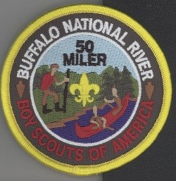 color photo of patch featuring scouts hiking and canoeing