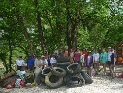 group photo of volunteers with tires and trash removed from the river