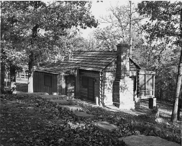 black and white photo of wooden cabin with stone chimney and screened porch