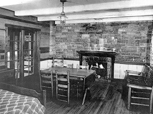 black & white photo of interior of cabin with stone fireplace wall at back and table and chairs at center