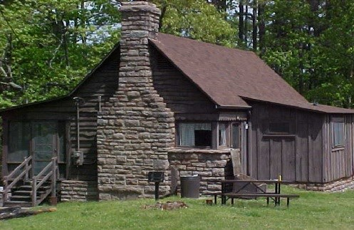 photo of brown cabin with stone chimney and board and batten siding