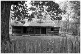 black & white photo of Collier Homestead cabin with paling fence in foreground
