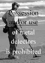 black & white photo of man using metal detector on the beach