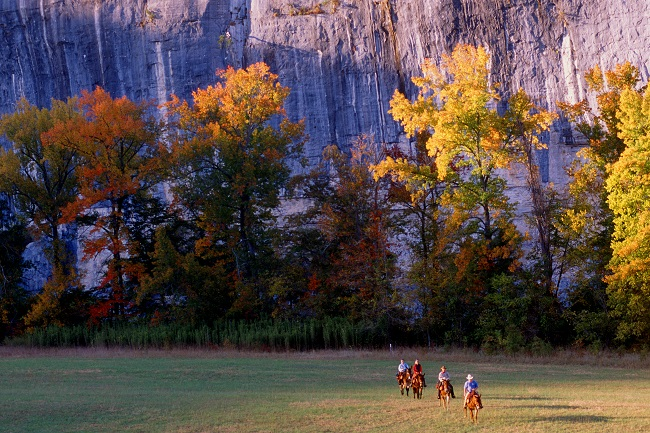 color photo with horseback riders on green grass at center bottom and trees with orange and yellow leaves with gray cliffs in background