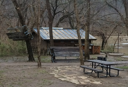 photo showing picnic table hanging in tree near park restroom with flooded river in background