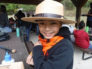 Boy wearing ranger hat eating at picnic table