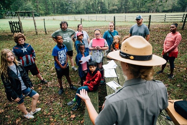 photo of children listening to park ranger (wearing flat hat) at bottom right