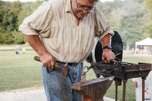 Blacksmith working metal on anvil with forge nearby.