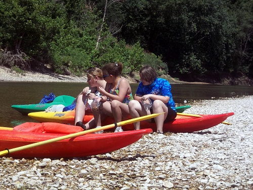 3 girls snacking while sitting on kayaks on gravel bar