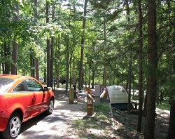 color photo of wooded campsite with red car at left and brown and white tent at right