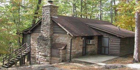 color photo of stone and board cabin constructed by the Civilian Conservation Corps