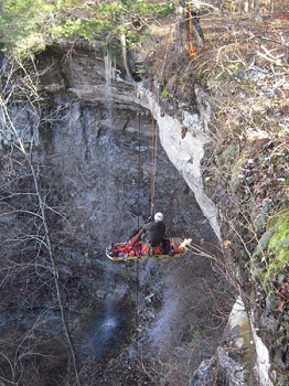 color photo of cliff with waterfall with rescuer on ropes with patient in litter