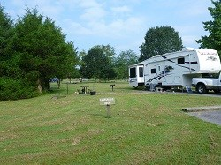 color photo of campsite with 5th wheel trailer at right