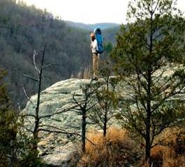 Man wearing large backpack standing on rocky cliff with view of forested valley.