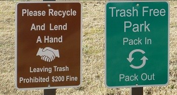 left: brown sign with handshake graphic Lend us a Hand, recycle text; right green sign with recycle symbol graphic, Trash Free Park text