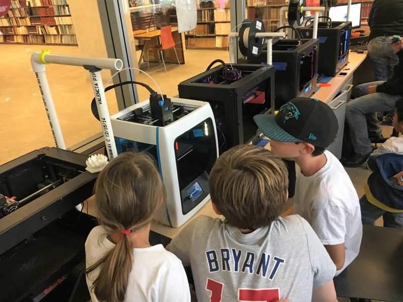 a group of students watch as a 3D printer works on a print at the Downtown Public Library Innovation Lab.