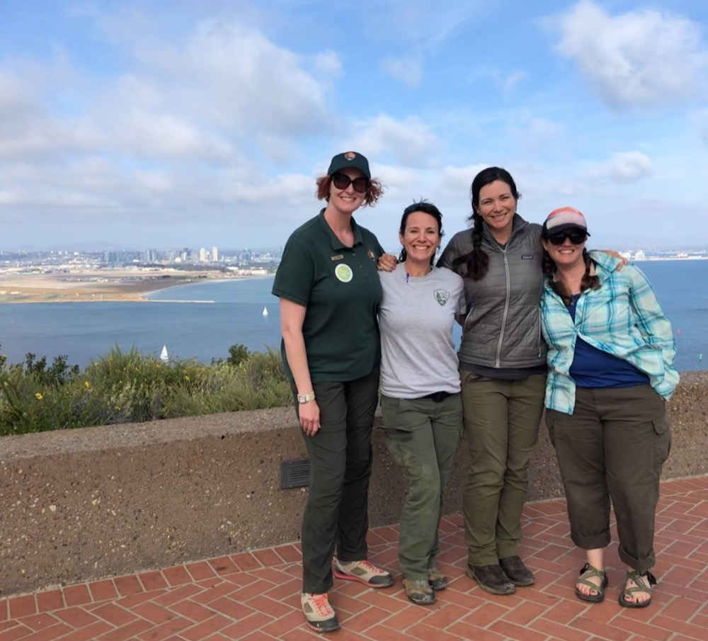 Four women pose for a picture in front of the backdrop of the city of San Diego. Two of the women are scientists from Cabrillo National Monument, and two of the women are scientists from Joshua Tree National Park.