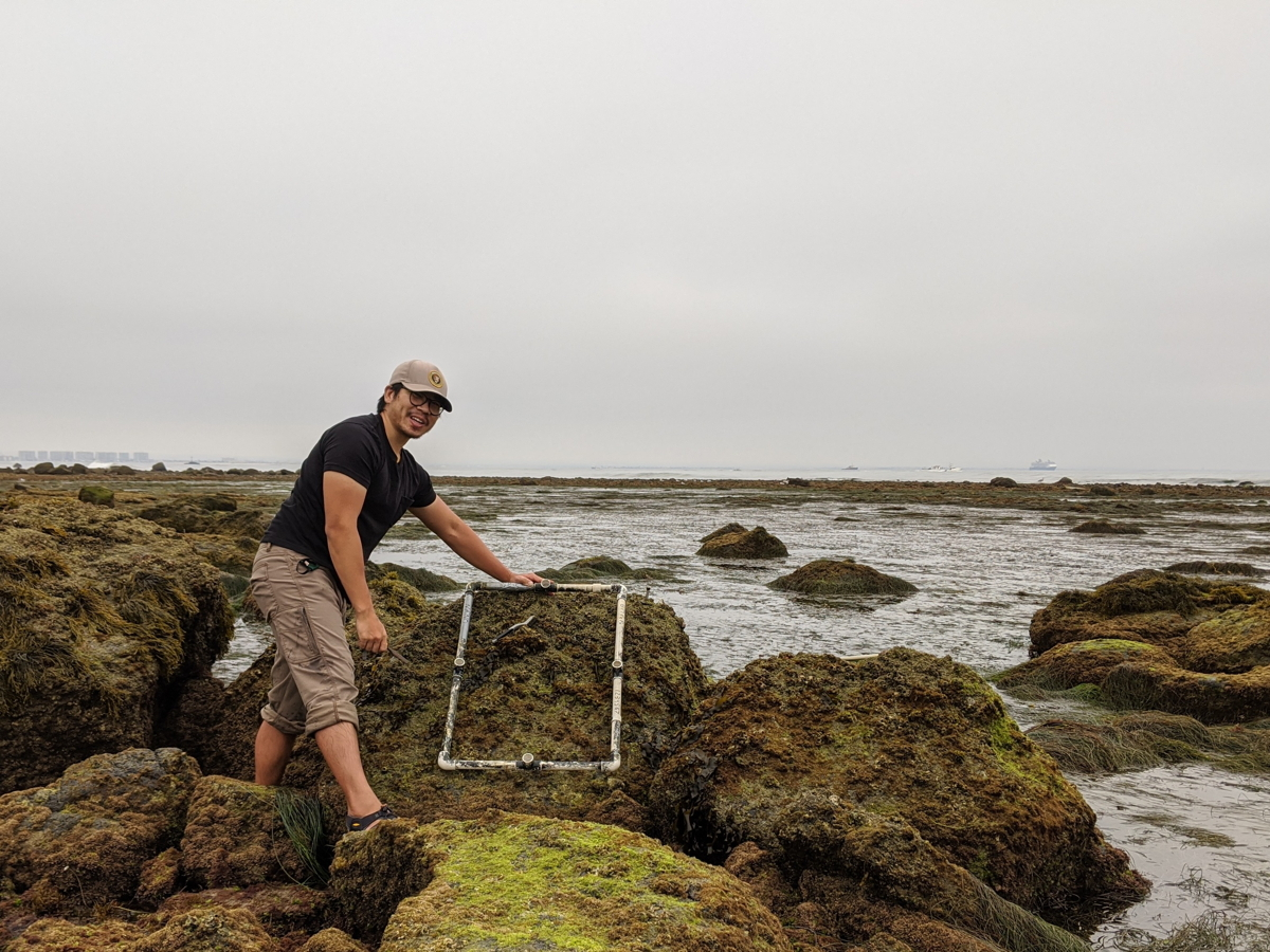 An Asian man with glasses wearing a ballcap and outdoor gear stands smiling in Cabrillo's tidepools at low tide. He is holding a square, white tool against one of the algae-covered rocks with an overcast sky in the background