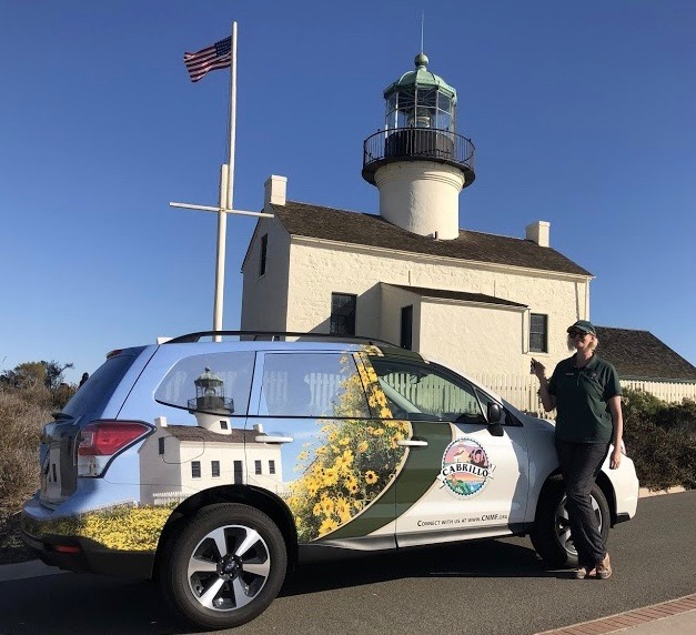 Outreach Coordinator Sam poses by the Cabrillo National Monument Foundation's outreach vehicle.