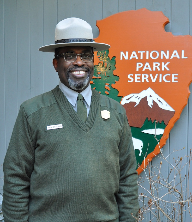 Uniformed ranger stands infront of the National Park Service Arrowhead