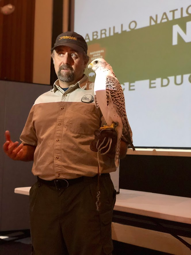 With a Gyrfalcon (Falco rusticolus) in hand, Naturally Speaking lecturer Charles Gailband speaks to attendees about the bird's lifestyle and adaptations.