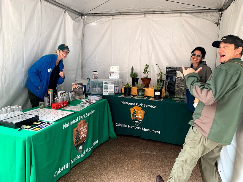 The science education and outreach team poses at their booth during the Science and Engineering Festival, complete with live plants, activities, and promotional materials.