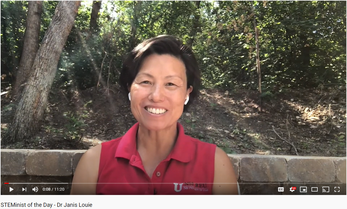A screenshot of a smiling Asian woman in a red University of Utah shirt with a stone wall and trees behind her.