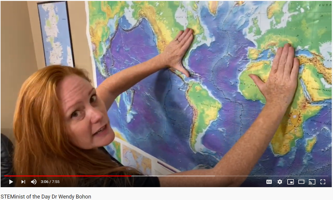 A screenshot of a smiling red-haired Caucasian woman in a black t-shirt who is gesturing to a world topographic map on the wall behind her.