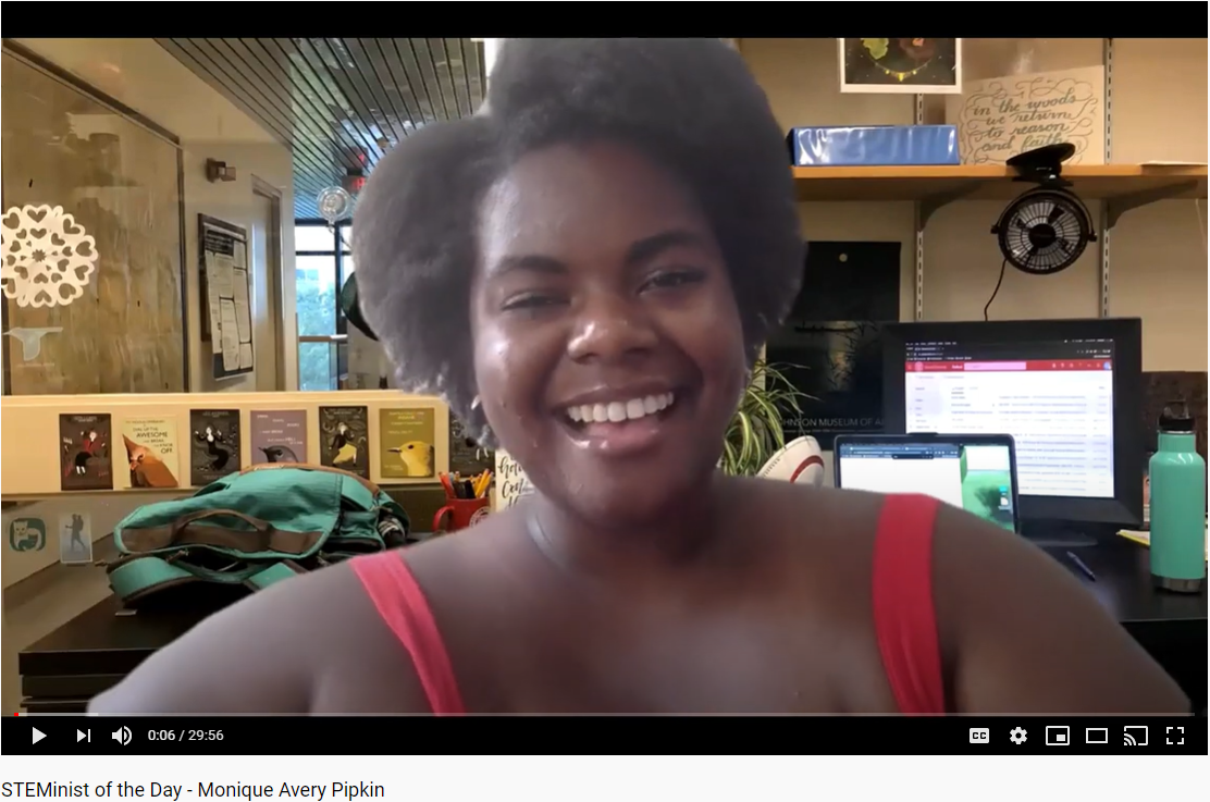 A screenshot of a smiling African American woman in a pink tanktop with her office in the background.