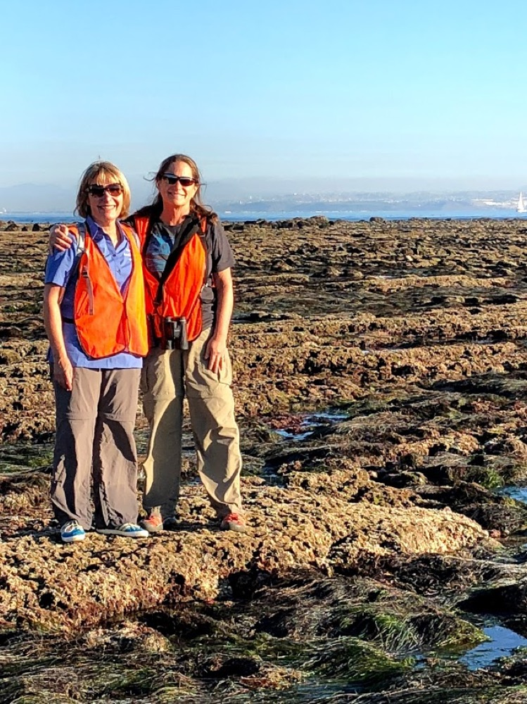 Two volunteers smiling for the camera in the tidepools at Cabrillo National Monument.