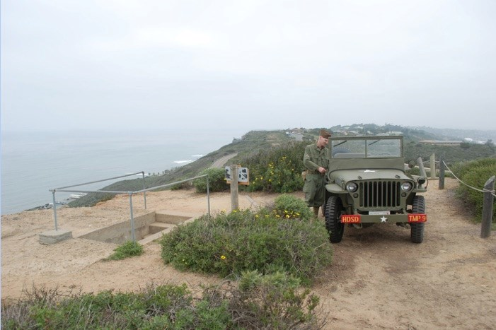 Volunteer in WWII clothing by jeep at the Bunker Entrance