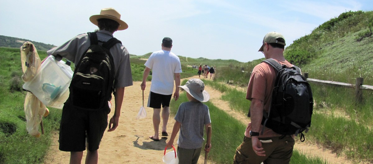 A ranger wearing a grey shirt and green shorts with a straw hat carries a clear plastic tote and a net. He is walking down the beach next to a child wearing a grey shirt and a man wearing a ball cap.