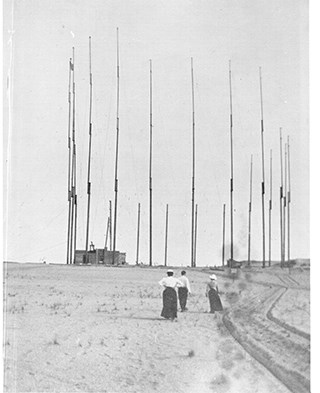 A black and white photo of a man and two women standing in an open area facing a building next to a tall circular array of thin antennas.