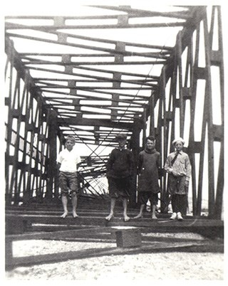 Four young boys stand inside a fallen square shaped metal frame radio tower.
