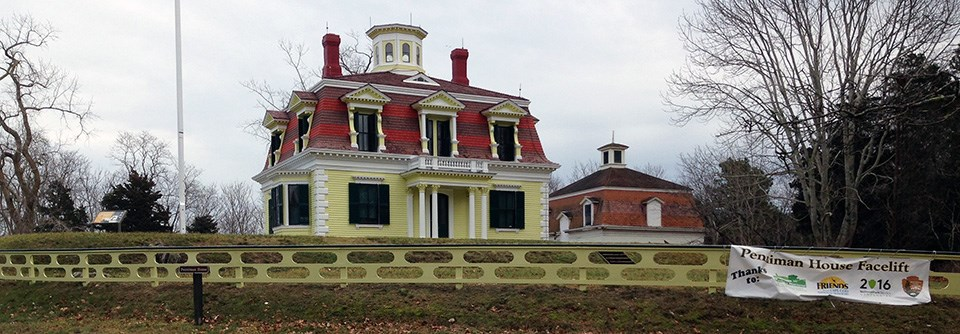 A bright yellow house with white trim sits a top a grassy hill surrounded by trees. There is an ornate wooden fence in the same colors surrounding the house.