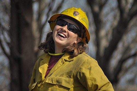 A woman wearing yellow fire resistant clothing looks at the camera while laughing.