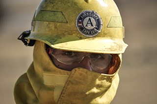 A person wearing a yellow face mask, yellow hard hat, and safety glasses.