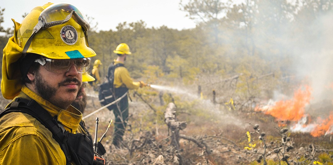 A man wearing yellow fire fighting equipment and safety glasses looks on as another person hoses down the fire with a water hose.